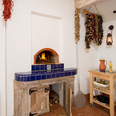 Tuscan terra-cotta tile and orange floor sunroom photo in DC Metro with a wood stove, a tile fireplace and a standard ceiling