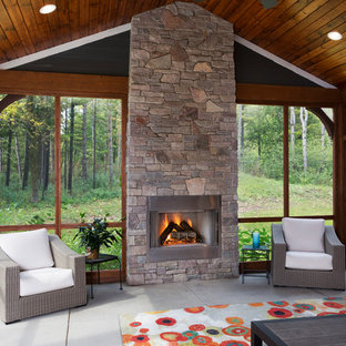 Inspiration for a large craftsman concrete floor and gray floor sunroom remodel in Milwaukee with a stone fireplace and a standard fireplace