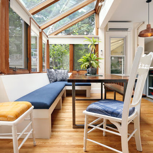 This is an example of a medium sized traditional conservatory in Boston with medium hardwood flooring and a glass ceiling.