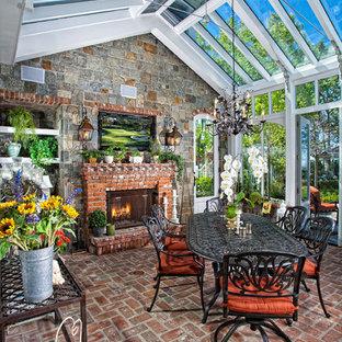 Idée de décoration pour une véranda tradition avec un sol en brique, un manteau de cheminée en brique, un plafond en verre et un sol rouge.