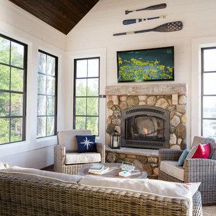 Diseño de galería costera, de tamaño medio, con suelo de madera oscura, estufa de leña, marco de chimenea de piedra y techo estándar