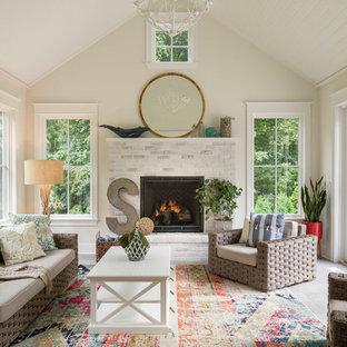 Cette photo montre une véranda bord de mer de taille moyenne avec une cheminée standard, un plafond standard, un sol gris, un sol en travertin et un manteau de cheminée en brique.