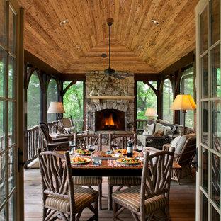 Idée de décoration pour une véranda chalet avec un sol en bois foncé, un manteau de cheminée en pierre, un plafond standard et un sol marron.
