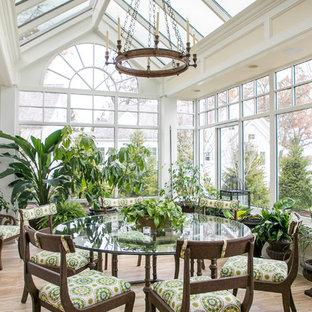 Cette photo montre une grand véranda chic avec un sol en bois brun, un plafond en verre, un sol marron et aucune cheminée.