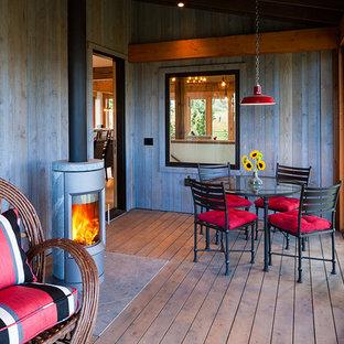 Immagine di una veranda stile rurale di medie dimensioni con parquet scuro, stufa a legna, cornice del camino in pietra e soffitto classico