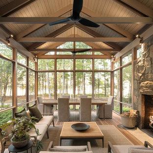 Idées déco pour une véranda contemporaine avec un sol en bois brun, une cheminée standard, un manteau de cheminée en pierre, un plafond standard et un sol marron.