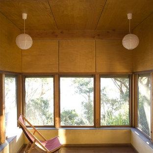 Cette image montre une véranda asiatique avec un sol en bois brun et un plafond standard.