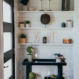 Inredning av ett klassiskt stort uterum, med klinkergolv i porslin, en standard öppen spis, en spiselkrans i tegelsten, tak och grått golv