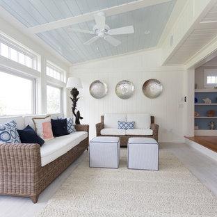 Cette photo montre une véranda bord de mer de taille moyenne avec un sol en bois clair, une cheminée double-face, un manteau de cheminée en carrelage et un plafond standard.