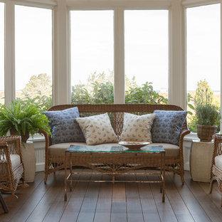 Réalisation d'une grand véranda marine avec un sol en bois foncé, aucune cheminée, un manteau de cheminée en brique et un plafond standard.
