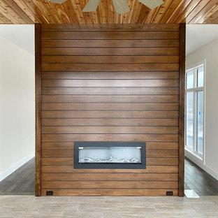 Cette image montre une véranda minimaliste de taille moyenne avec une cheminée double-face et un manteau de cheminée en bois.