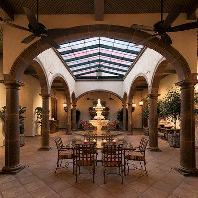 Sunroom - huge mediterranean terra-cotta tile sunroom idea in Santa Barbara with a skylight