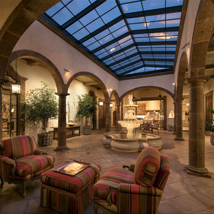 This is an example of an expansive mediterranean conservatory in Santa Barbara with terracotta flooring and a skylight.