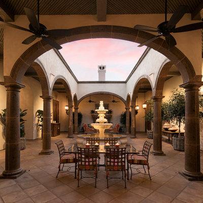 Sunroom - huge mediterranean terra-cotta tile sunroom idea in Santa Barbara