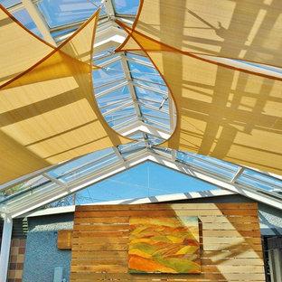 Cette photo montre une grand véranda moderne avec un puits de lumière et un sol en bois clair.