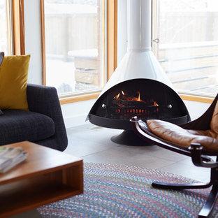Bild på ett mellanstort 60 tals uterum, med klinkergolv i porslin, en hängande öppen spis, takfönster och grått golv