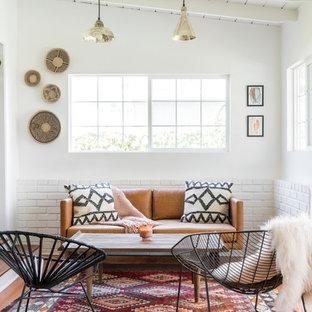 Cette image montre une grand véranda vintage avec aucune cheminée, un plafond standard, un sol en bois brun et un sol marron.