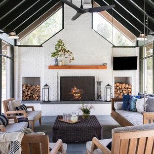 Idées déco pour une grand véranda campagne avec un sol en ardoise, une cheminée standard, un manteau de cheminée en brique, un puits de lumière et un sol gris.