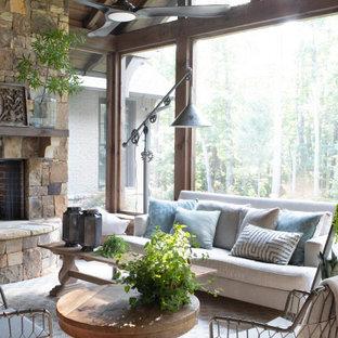 Idée de décoration pour une grand véranda champêtre avec une cheminée standard, un manteau de cheminée en pierre et un plafond standard.