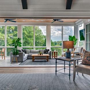 Aménagement d'une véranda campagne de taille moyenne avec un sol en bois brun, aucune cheminée, un plafond standard et un sol marron.
