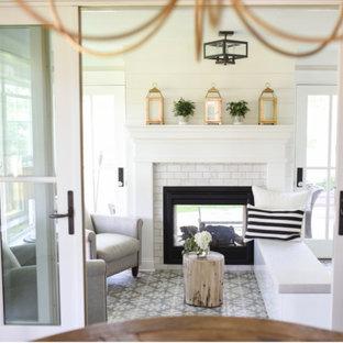 Inspiration pour une véranda traditionnelle avec un sol en carrelage de porcelaine, une cheminée double-face, un manteau de cheminée en carrelage et un sol gris.