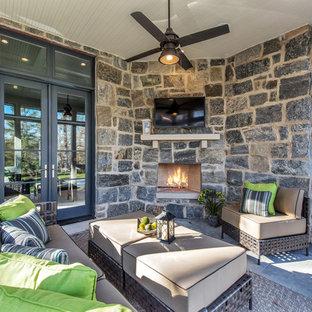 Foto di una grande veranda chic con camino classico, cornice del camino in pietra e soffitto classico