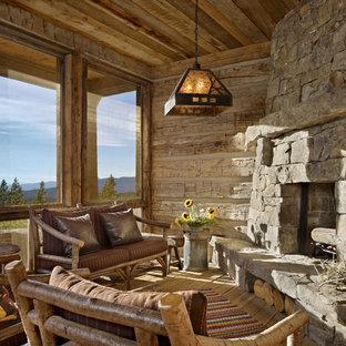 Cette photo montre une véranda montagne de taille moyenne avec un sol en bois brun, un manteau de cheminée en pierre, un plafond standard et une cheminée d'angle.