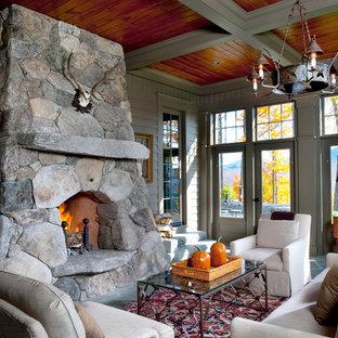 Réalisation d'une grand véranda tradition avec un sol en ardoise, une cheminée double-face, un manteau de cheminée en pierre et un plafond standard.
