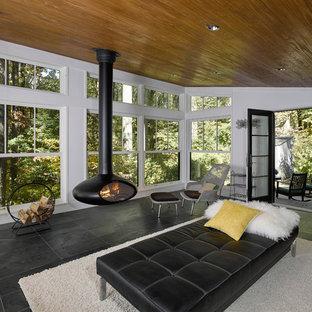 Inspiration för mellanstora moderna uterum, med skiffergolv, en hängande öppen spis, tak och svart golv