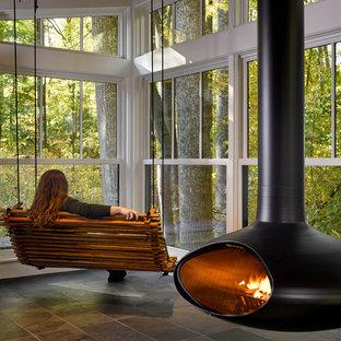 Inspiration pour une véranda minimaliste de taille moyenne avec un sol en ardoise, cheminée suspendue, un plafond standard et un sol noir.
