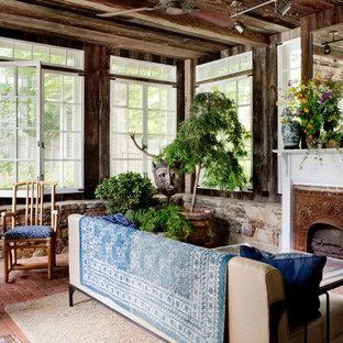 Idée de décoration pour une véranda champêtre avec un sol en brique, une cheminée standard, un plafond standard et un sol rouge.