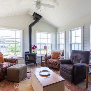 Photo of a coastal conservatory in Other with medium hardwood flooring, a wood burning stove, a standard ceiling and brown floors.