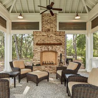Cette image montre une grand véranda traditionnelle avec une cheminée standard, un manteau de cheminée en brique et un plafond standard.