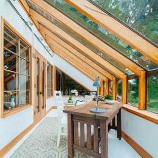 Aménagement d'une véranda exotique avec aucune cheminée, un plafond en verre et un sol gris.
