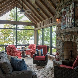 Exempel på ett stort rustikt uterum, med travertin golv, en standard öppen spis, en spiselkrans i sten, tak och beiget golv
