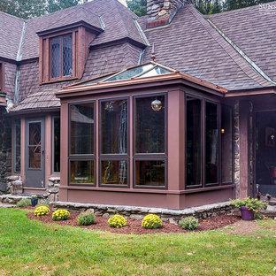 Cette image montre une petit véranda traditionnelle avec un sol en bois foncé, aucune cheminée et un plafond en verre.