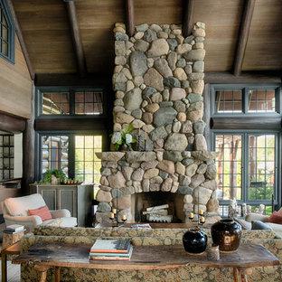 Aménagement d'une véranda montagne avec un sol en bois foncé, une cheminée standard, un manteau de cheminée en pierre et un plafond standard.