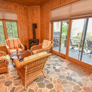 Imagen de galería rural, de tamaño medio, con suelo de pizarra, estufa de leña, techo estándar y suelo multicolor