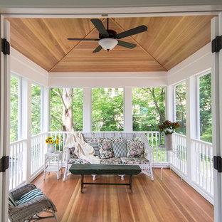 Cette image montre une véranda victorienne de taille moyenne avec un sol en bois clair, une cheminée standard et un plafond standard.