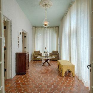 Idées déco pour une véranda méditerranéenne avec un sol en carreau de terre cuite, un plafond standard et un sol orange.
