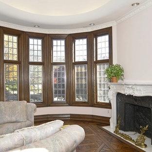 Inredning av ett klassiskt stort uterum, med mörkt trägolv, en standard öppen spis, en spiselkrans i gips, tak och brunt golv