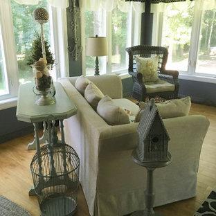 Aménagement d'une véranda romantique de taille moyenne avec un sol en bois clair, aucune cheminée, un plafond standard et un sol marron.