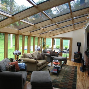 Mid-sized trendy light wood floor sunroom photo in Chicago with a wood stove, a metal fireplace and a glass ceiling