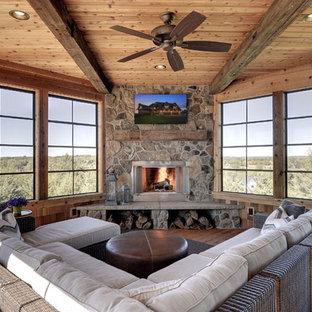 Idée de décoration pour une grand véranda chalet avec un sol en bois brun, une cheminée d'angle, un manteau de cheminée en pierre, un plafond standard et un sol marron.