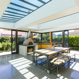 Foto di una veranda moderna di medie dimensioni con pavimento in cemento, stufa a legna, cornice del camino in cemento, lucernario e pavimento grigio