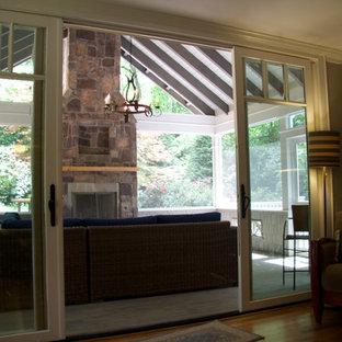 Sunroom - mid-sized contemporary medium tone wood floor and brown floor sunroom idea in Atlanta with a standard fireplace, a stone fireplace and a standard ceiling