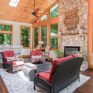 Idéer för ett rustikt uterum, med mörkt trägolv, en öppen vedspis och takfönster