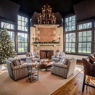 Cette photo montre une grand véranda chic avec un sol en bois brun, une cheminée d'angle, un manteau de cheminée en pierre, un plafond standard et un sol marron.