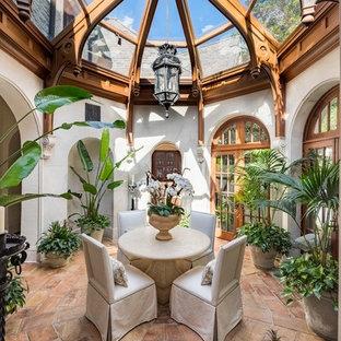 Ejemplo de galería mediterránea con suelo de baldosas de terracota, techo de vidrio y suelo marrón
