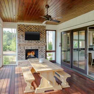Exemple d'une véranda nature de taille moyenne avec un sol en bois foncé, une cheminée standard, un manteau de cheminée en brique, un plafond standard et un sol marron.